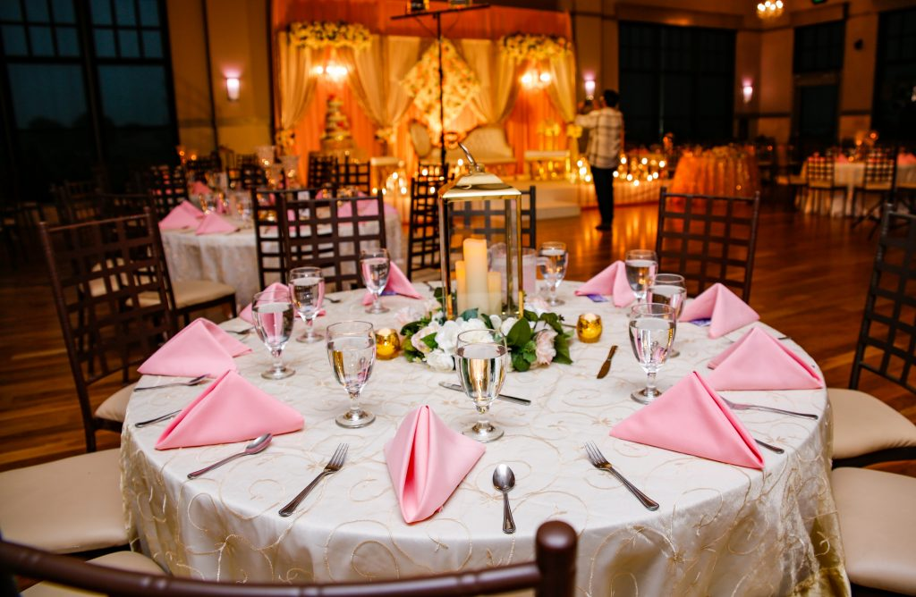Pink napkins, sequin linens and candle lit flower centerpieces