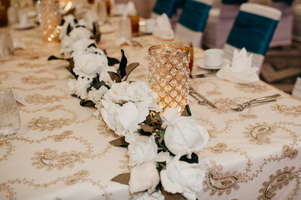 Gold votive candles and white wedding flowers