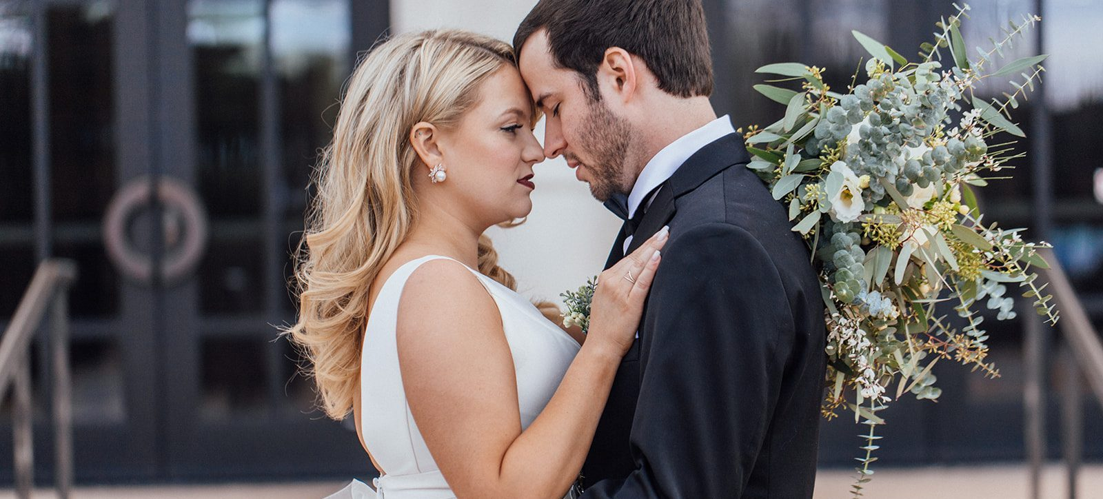 Wedding day kiss with garden and gathered bridal bouquet
