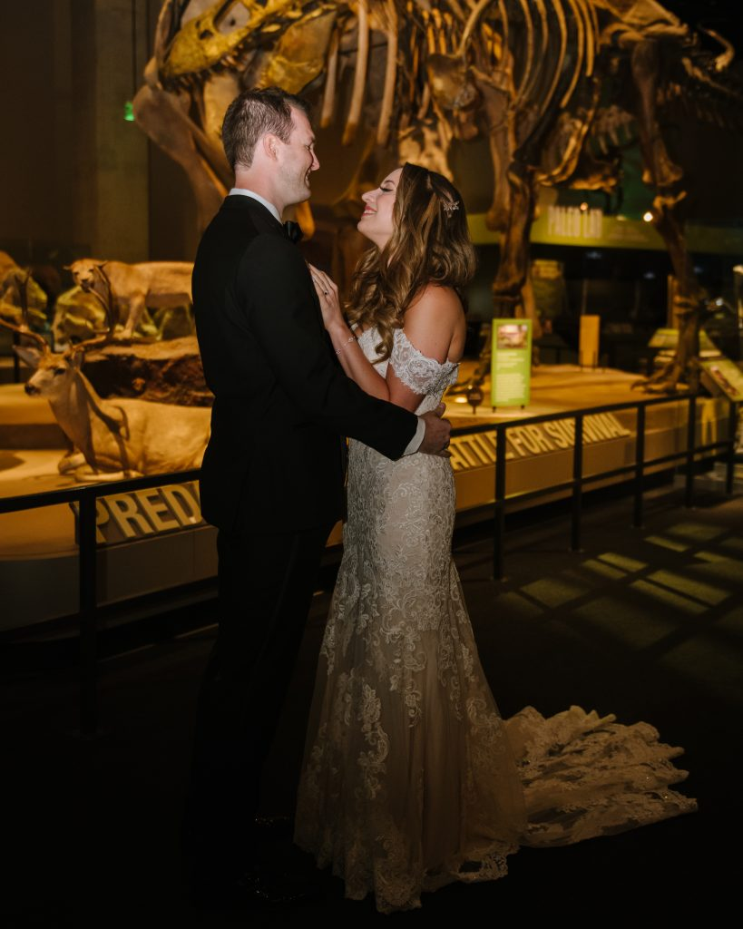 Bride and groom embrace in front of dinosaur exhibit