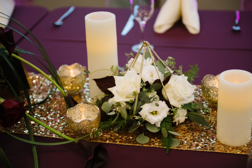 Geometric shapes and gold votive candles with small flower centerpieces